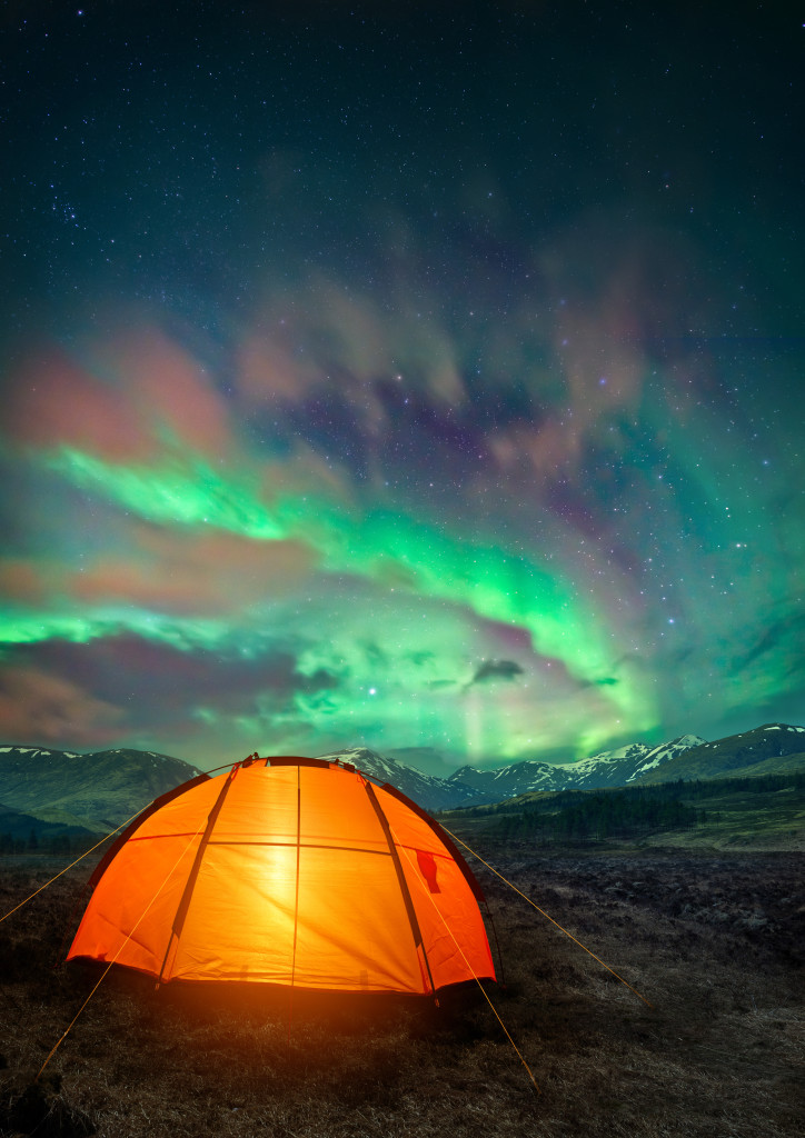 A camping tent glowing under the Northern Lights. Night time camping scene.